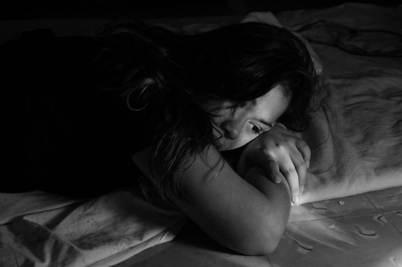 Женщина грустит в постели